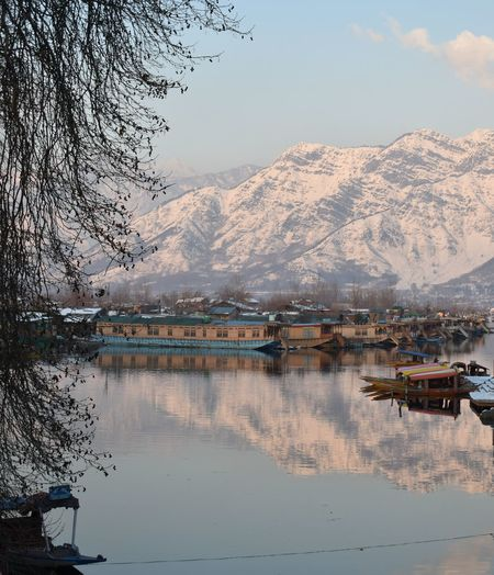 The reflection of snow capped Zabarwan mountain range in the Dal Lake adds to the beauty of the area. Water Mountain Lake Tree Nautical Vessel Reflection Beach Sky Landscape Mountain Range