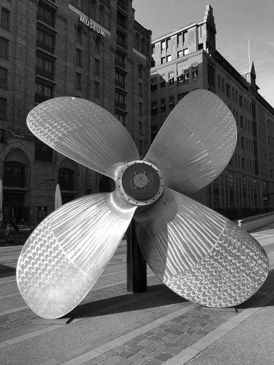 Modern sculpture on street against buildings in city