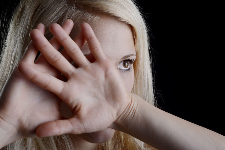 Close-up of young woman covering face against black background