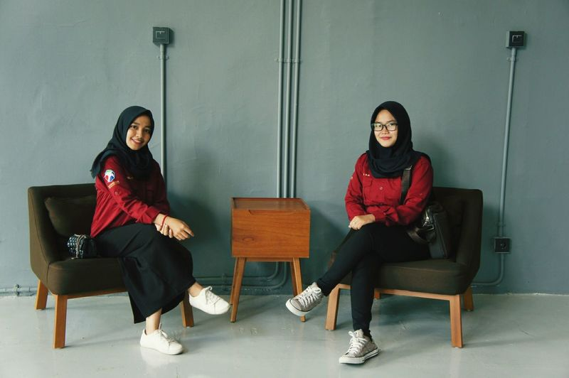 Portrait of female friends smiling while sitting on chairs against wall