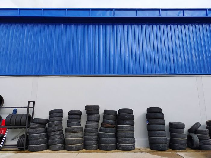 View of tires stacked by wall outdoors