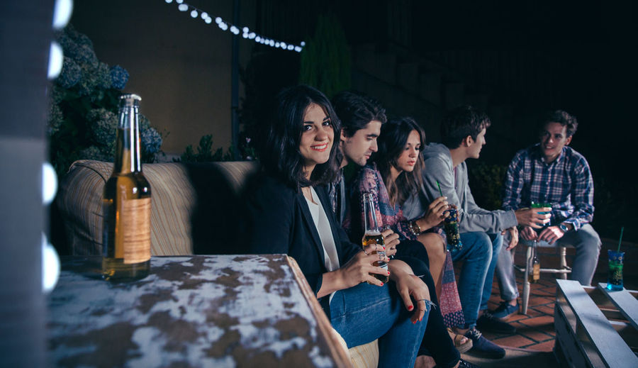 Portrait of smiling young woman sitting and holding a beer while her friends talking in a outdoors party. Friendship and celebrations concept. Beer Celebration Friends Fun Happiness Happy Horizontal Laughing Light Sitting Young Alcohol Bottle Cheerful Drink Entertainment Five People Friendship Group Night Nightlife Outdoors Party People Sofa