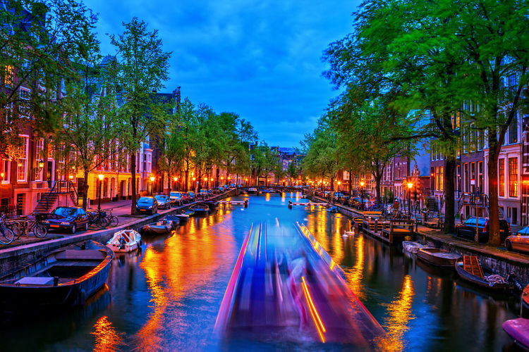 Panoramic view of canal in city at dusk