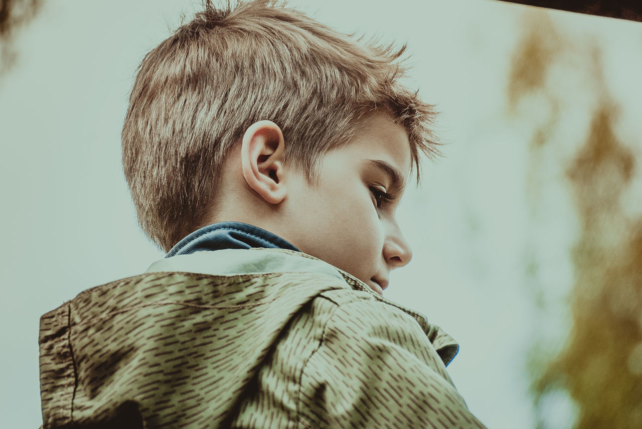 Low Angle View Of Boy Looking Away While Standing Against Sky