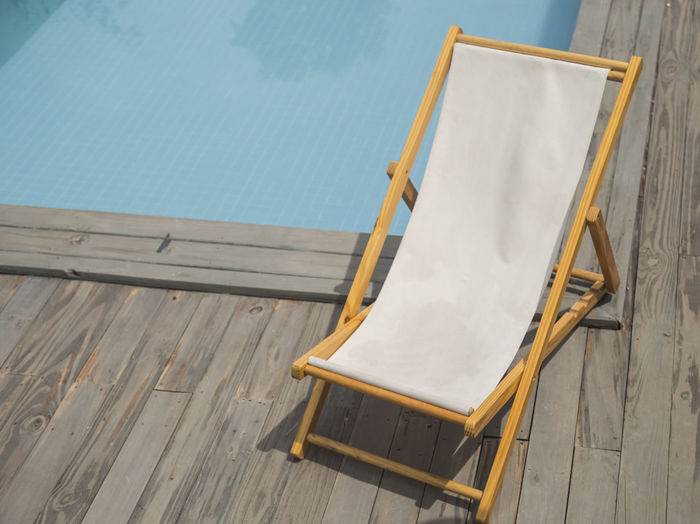High angle view of empty lounge chair against swimming pool