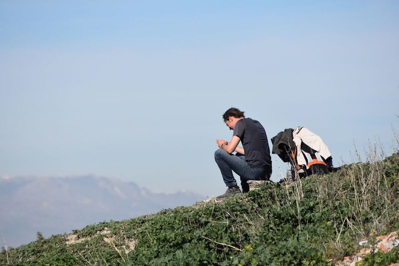 Low angle view of man sitting on rock over hill against sky
