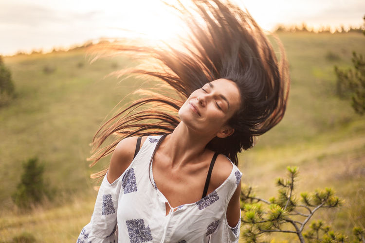 Beautiful young woman tossing hair while standing on field