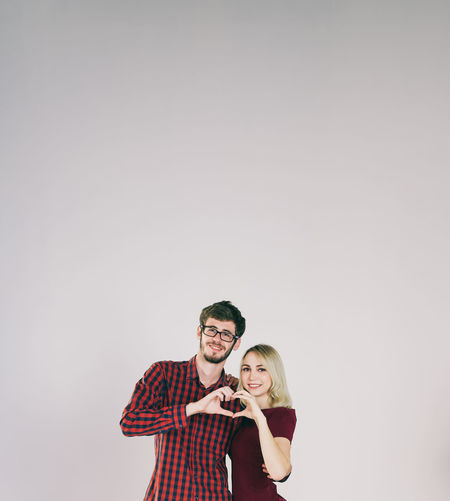 Portrait of young couple making heart shape standing against wall