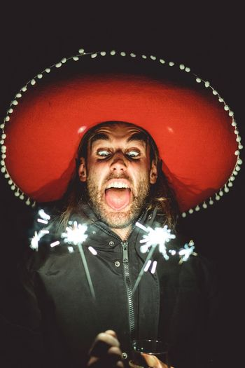Happy new year! Event Night Tongue Costume Crazy Party New Year Face Fireworks Fire Sparklers Sparkler Rocknroll Strange Mimic Sombrero Big Hat Mexican Indoors  One Person Representation Front View Portrait Male Likeness Low Angle View Celebration Black Background Illuminated