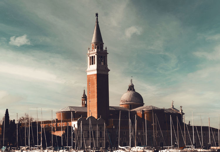 Tower of building against cloudy sky in venice