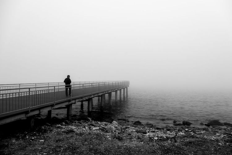 Man standing on railing by sea against sky