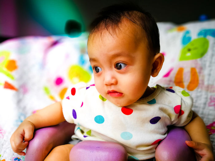 Close-up of cute baby girl drooling at home