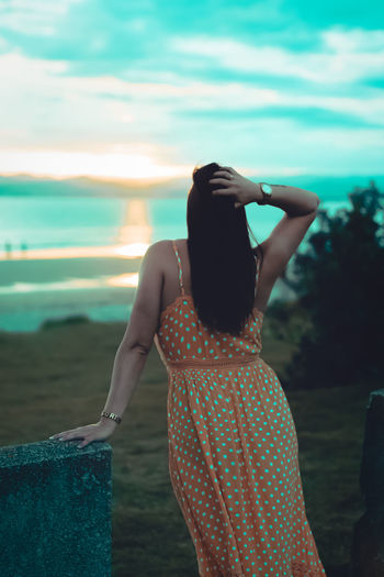 Rear View Of Woman With Hand In Hair Looking At Sea During Sunset