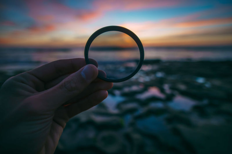 Cropped image of hand holding lens at beach during sunset