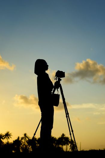 Scenic view of photographer silhoutte on the sunset background. Photographer Photography Alone Wallpaper Background Malaysia ASIA Filming Men Full Length Standing Camera - Photographic Equipment Silhouette Sunset Holding Tripod Side View Photographing Photography Themes