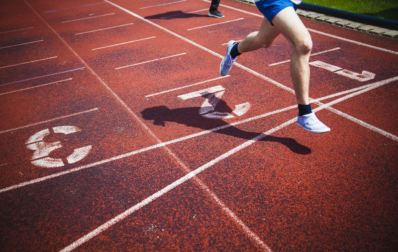 Low section of athlete running on sports track