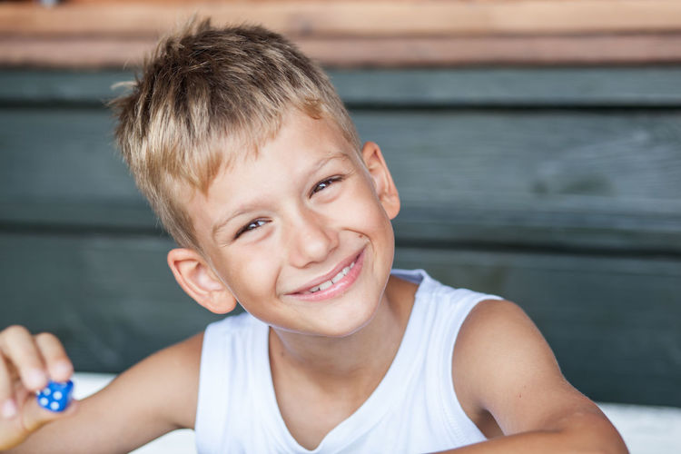 Portrait Of Smiling Boy Holding Blue Dice At Home