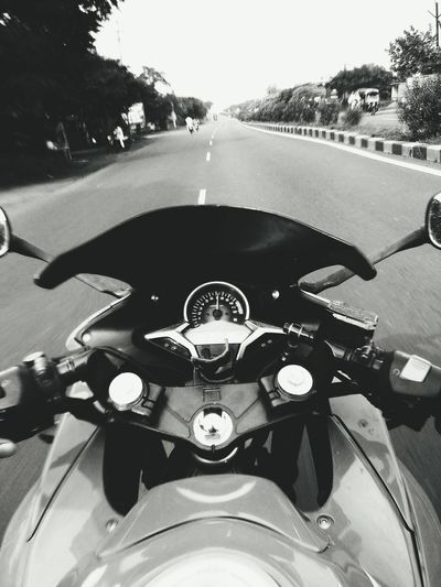 Close-up of person riding motorcycle on road