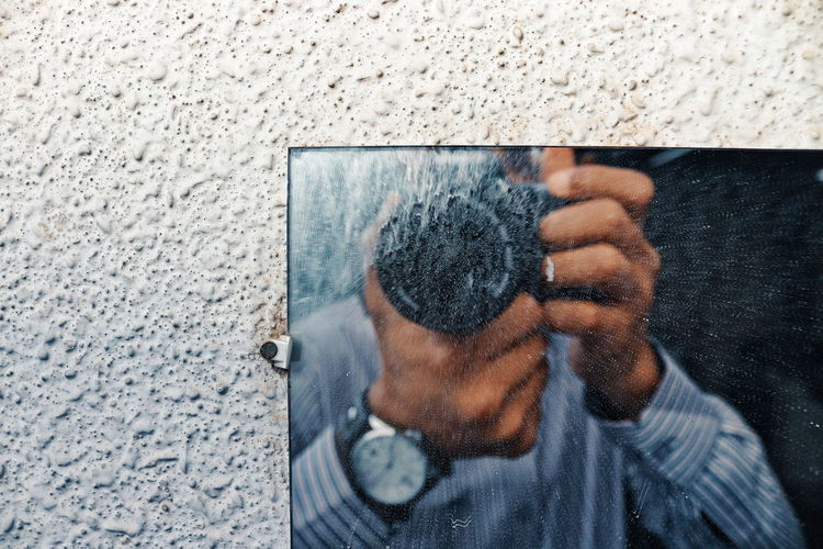 Close-up of man photographing while standing against mirror