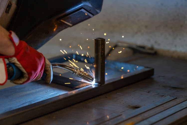 Man working on table in illuminated factory