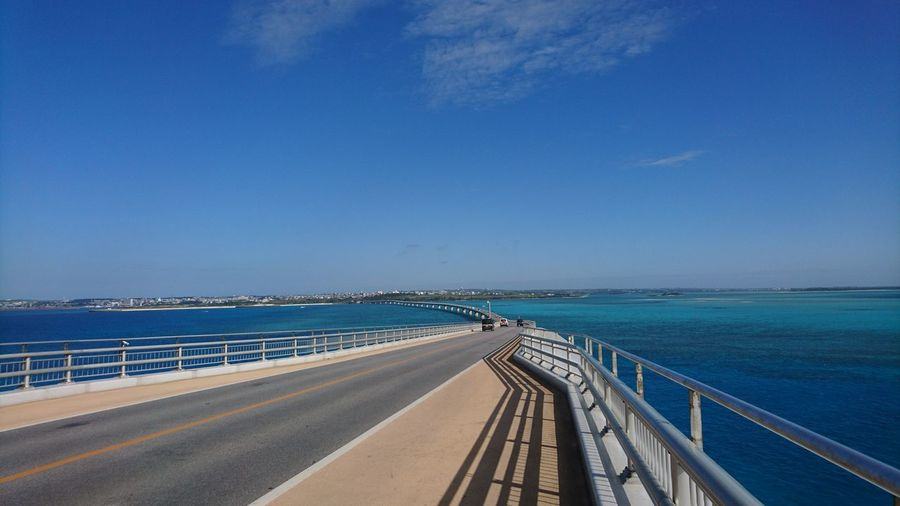 View of road by sea against blue sky