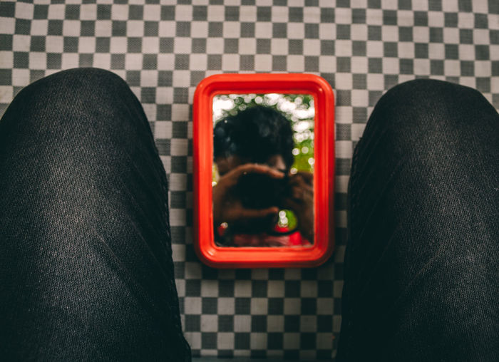 Reflection of man photographing on mirror amidst knees