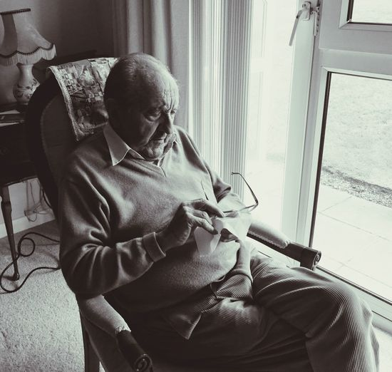 High Angle View Of Senior Man Cleaning Eyeglasses While Sitting On Armchair