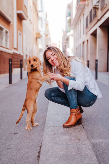 Full length portrait of woman with dog in city