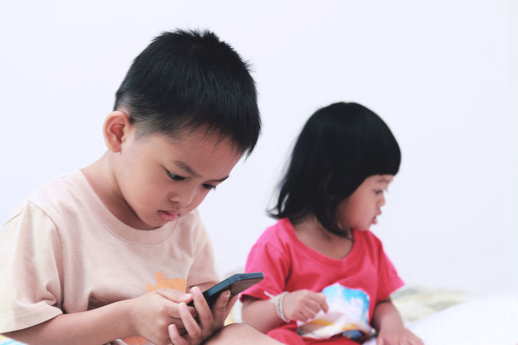 Boy Using Mobile Phone With Sister Against White Wall At Home