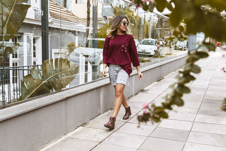 Young Woman Walking On Sidewalk By Glass Building