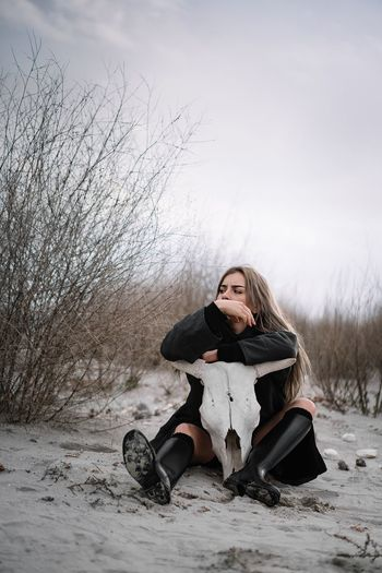 Woman sitting on sand on the beach in winter