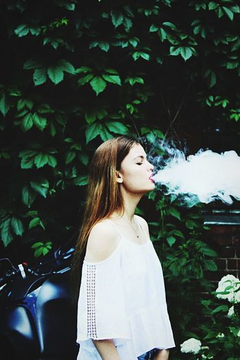 Woman exhaling smoke against trees