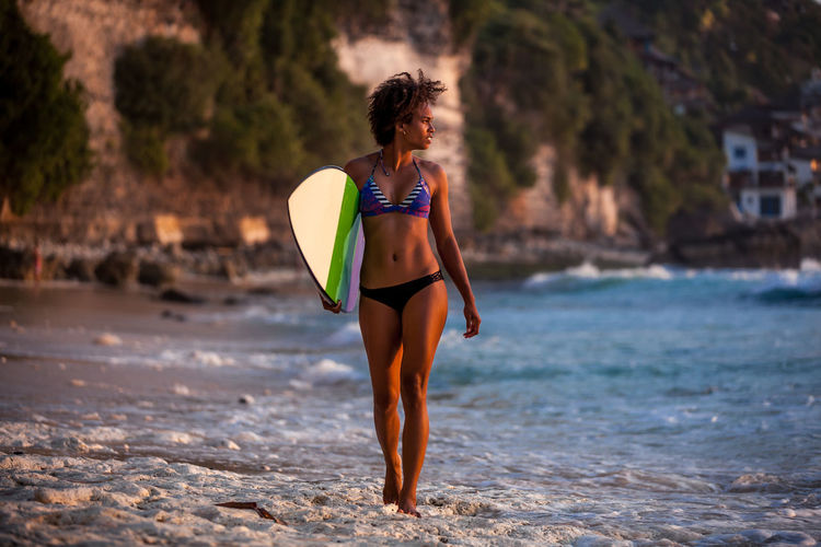 Full Length Of Woman With Surfboard Walking At Beach