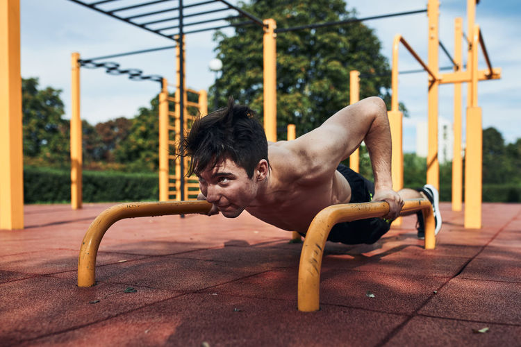 Young shirtless man bodybuilder doing push-ups on a parallel bars during his workout