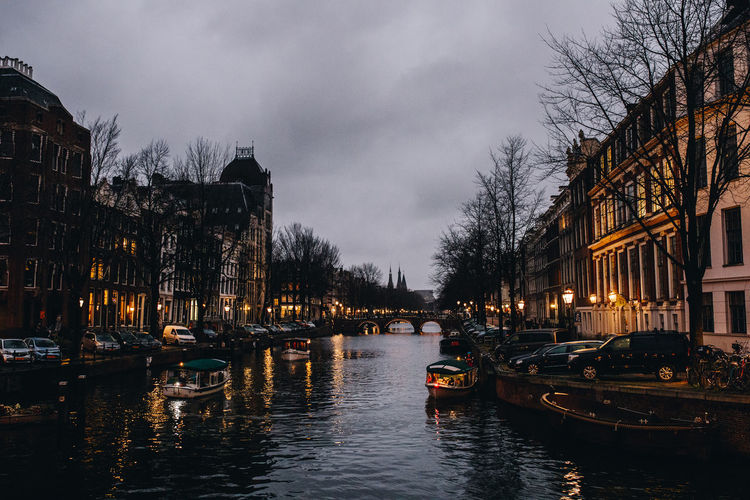 Boats in canal amidst buildings in city at dusk