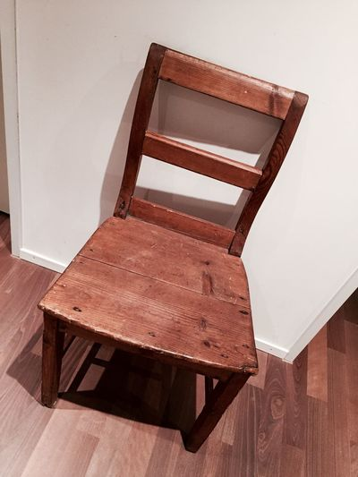High Angle View Of Wooden Chair Against Wall At Home