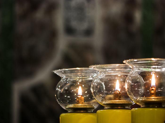 Close-Up Of Illuminated Diya In Jars