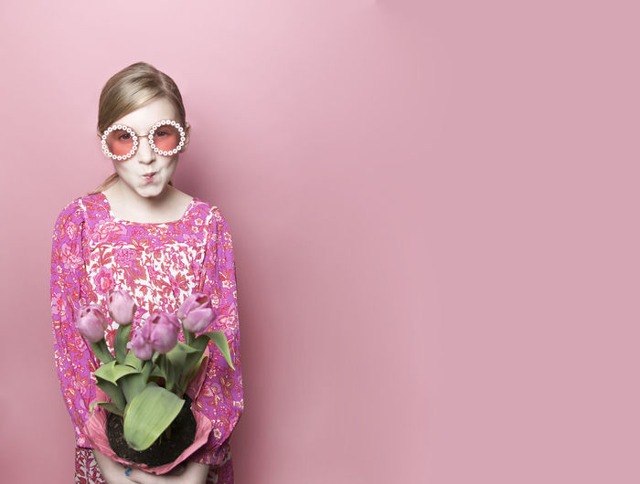 Young woman standing by pink flower against white background