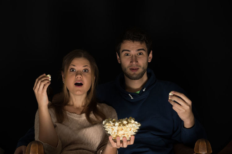 Portrait of young couple having popcorn while sitting against black background