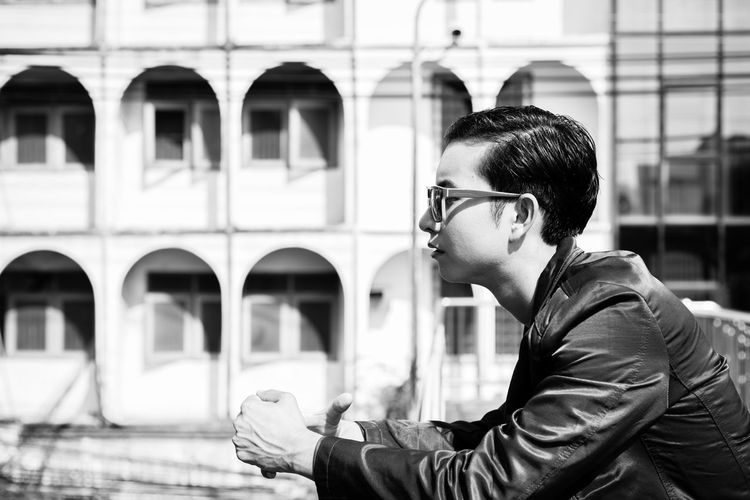 He is thinking something about his future life. Determined Man Overpass Smart Stress Stylish Thinking Black And White Photo Building Background Businessman Day Depressed Glasses Guy Handsome Leather Jacket Lifestyles Model Outdoors Serious Stressed Sunglasses Thinking About Life Young Adult Young Men
