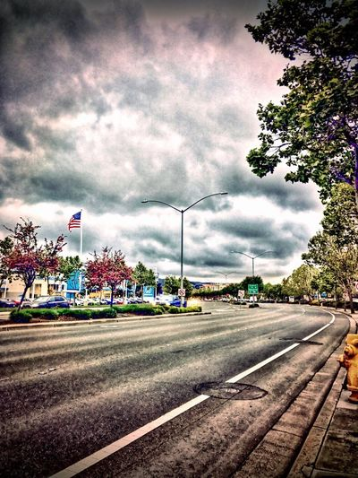 Road Outdoors EyeEmNewHere Rainy Days Marina Wainwright Roadsidephotography Sky Cloud - Sky Tree Road Day Flag Transportation No People Architecture Live For The Story Visual Feast The Street Photographer - 2017 EyeEm Awards The Great Outdoors - 2017 EyeEm Awards The Architect - 2017 EyeEm Awards The Photojournalist - 2017 EyeEm Awards EyeEmNewHere