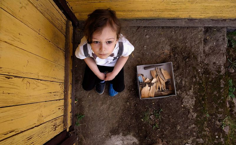 The biggest treasure Ways Of Seeing Different Shoes Boring Bored Playing Melancholy Thoughtful Calmness Rural Scene Relaxation Kid Summer From Above  Boy Leisure Activity Elementary Age Sitting Dreaming Treasure Wooden Sticks Child Childhood Portrait Closed Door The Portraitist - 2018 EyeEm Awards Creative Space