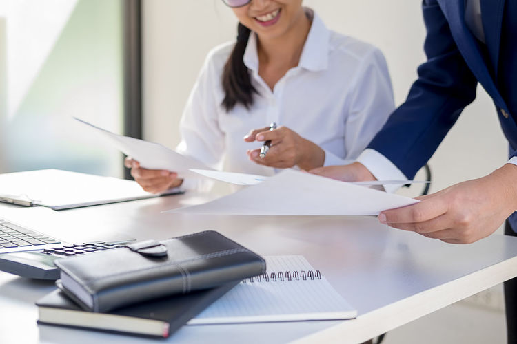 Midsection of businesswoman with colleague working at office
