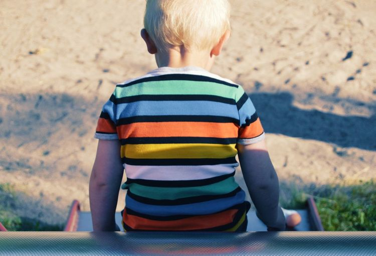 Rear view of boy sitting on slide at playground