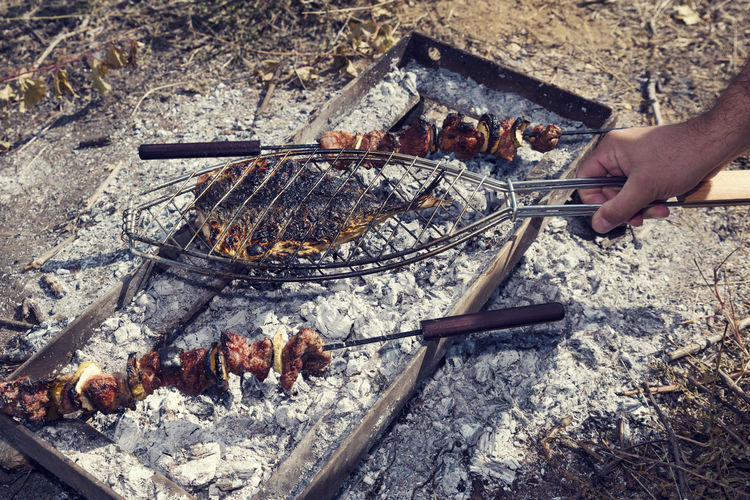 Low angle view of people on barbecue grill