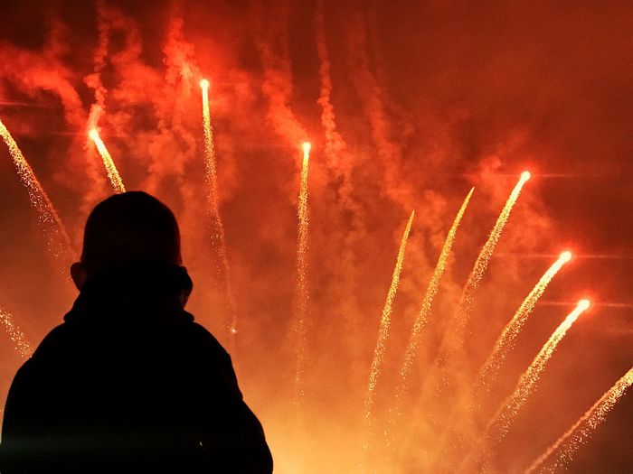 Silhouette person looking at firework display at night
