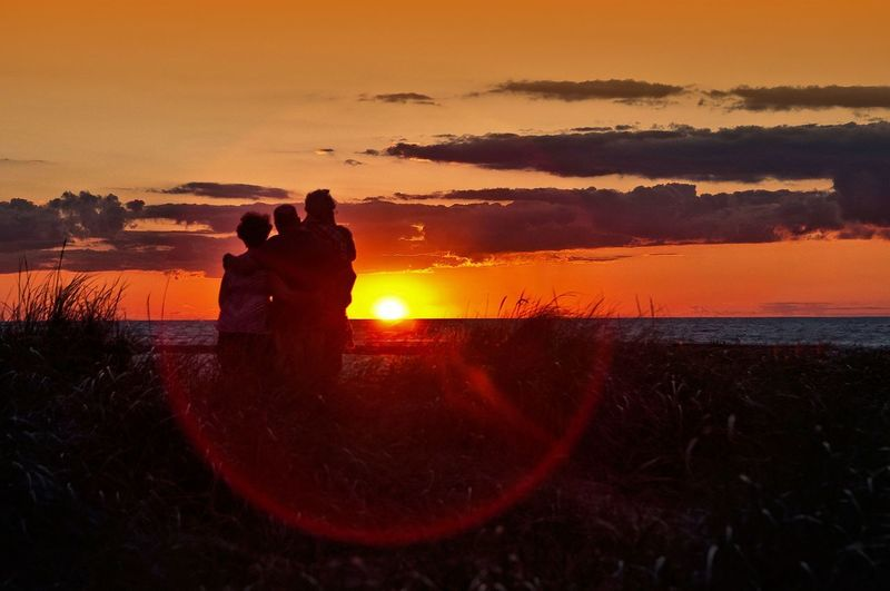 Silhouette people on beach against orange sky during sunset