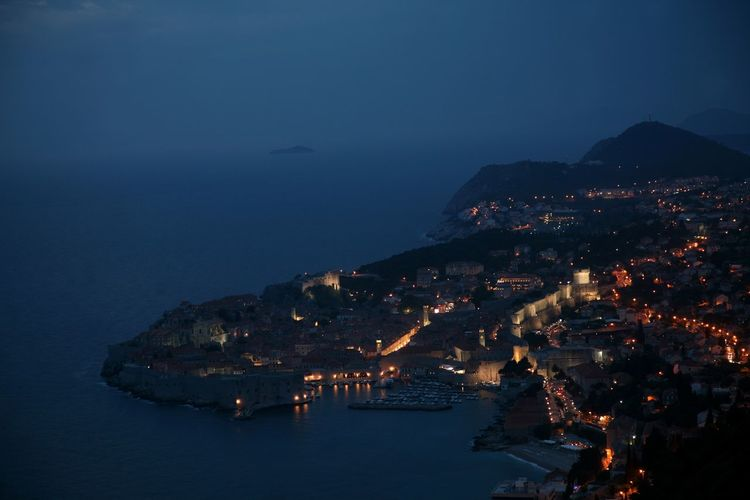 High angle view of illuminated townscape by adriatic sea at night