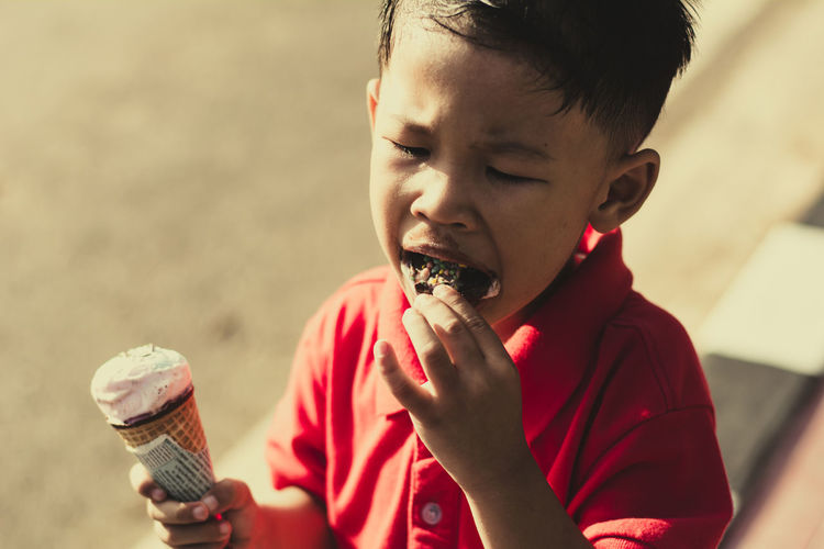Kid eating ice cream in waffles cone and winking on park outdoor background. Child Childhood Males  Holding Boys One Person Men Focus On Foreground Sweet Food Sweet Eating Food Ice Cream Food And Drink Ice Cream Cone Frozen Food Cone Offspring Frozen Temptation Innocence Outdoors