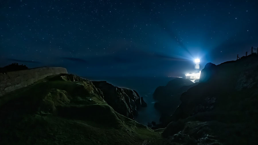 Scenic view of rocks at sea against sky at night